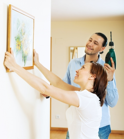 Happy middle-aged couple choosing place for picture in frame on the wall photo