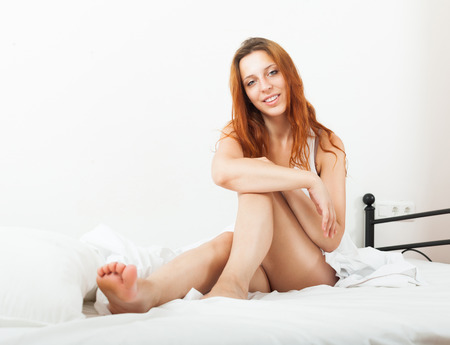 awaking: Cheerful red-haired young woman awaking on white sheet in her bed