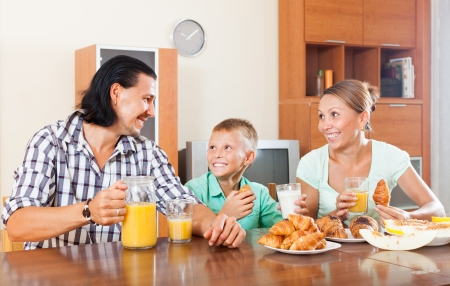 Happy couple with son having breakfast with croissants in morning at home interior photo