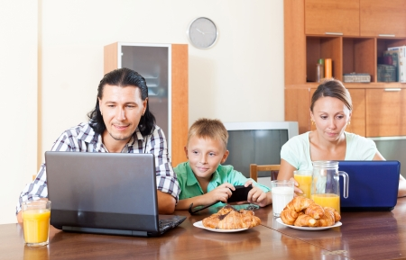 electronic devices: Happy adult couple with teenager having breakfast with electronic devices in morning at home interior