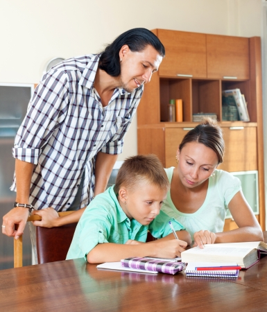 Teenager schoolboy and parents together doing homework in home  photo