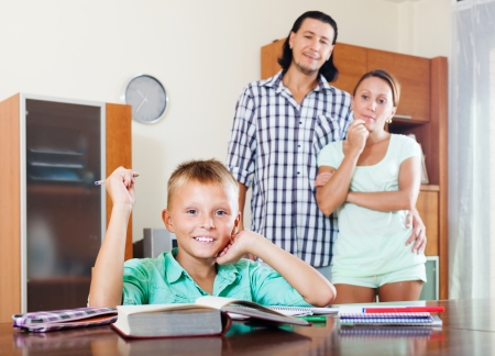 Happy  teenager schoolboy doing homework against  parents in home photo