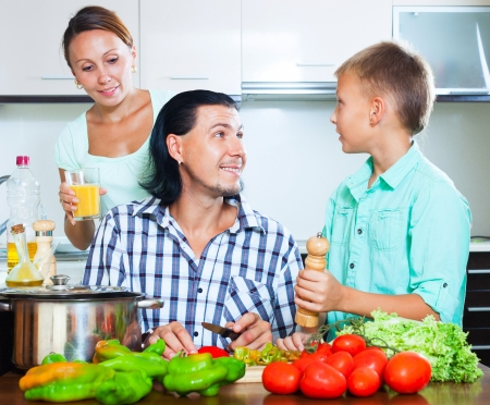 Happy couple with teenager child cutting the vegetables for salad in home kitchen photo