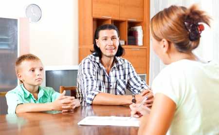parent and teenager: Son and father answer questions of a social worker in home Stock Photo
