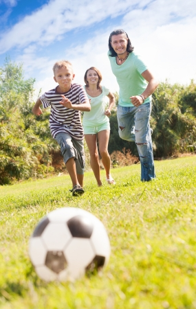 teenage boy with happy parents playing in soccer in summer park photo