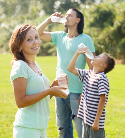 ordinary  couple with teenager drinking water from plastic bottles   photo