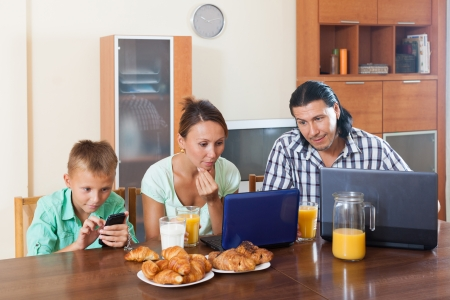 Happy family of three having breakfast at home   photo
