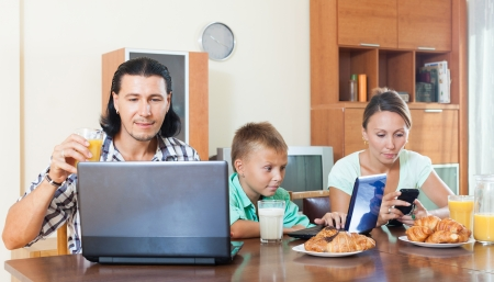 Happy couple with a kid smart teenager with a device during breakfast in a house interior