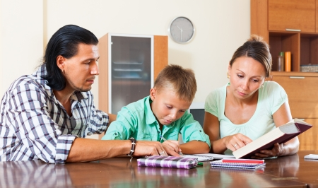 Teenager schoolboy doing homework with parents photo