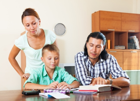 parents and teenager helping with homework in home interior photo