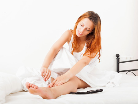 Beautiful girl cares for toenails with scissors in bed  at home Stock Photo - 22482480