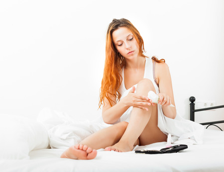 Young woman caring for legs with cosmetic cream in bed Stock Photo - 22482481