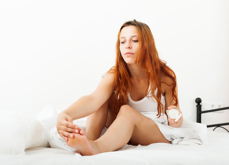 Long-haired young woman putting cream on feet at home Stock Photo - 22482482