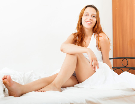 Long-haired woman wakes up in her bed photo
