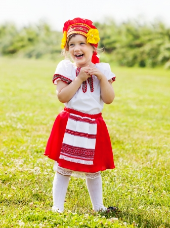 child in traditional folk clothes on grass photo