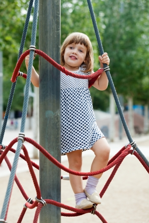 child in dress climbing at ropes on playground  in summer photo