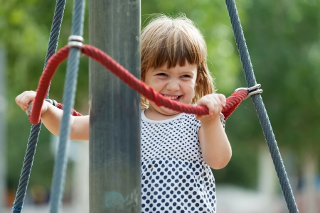 adroitness:  laughing girl climbing at ropes on playground area