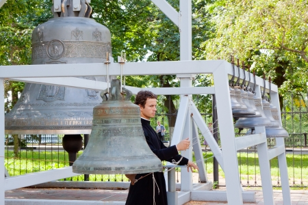 knell: YAROSLAVL, RUSSIA - JULY 28: Monk is rings the bell of Dormition cathedral in July 28, 2012 in Yaroslavl, Russia. Dormition Cathedral was built in 1215 and demolished in 1937. Now there is recovery