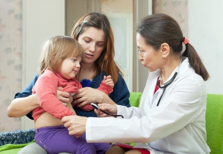children's doctor: mature childrens doctor examining 2 years baby with  stethoscope