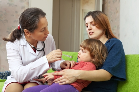 children's doctor: childrens doctor looks throat of 2 years baby Stock Photo