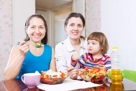 Two happy women with baby eats vegetables salad photo