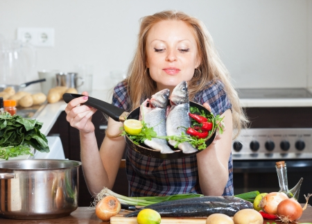 fryingpan:  girl with raw seabass  in frying pan at home kitchen  Stock Photo
