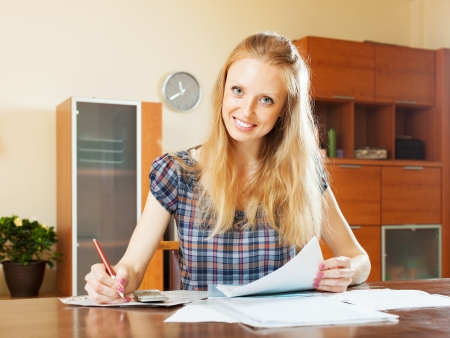 Happy woman fills in the questionnaire at  home photo