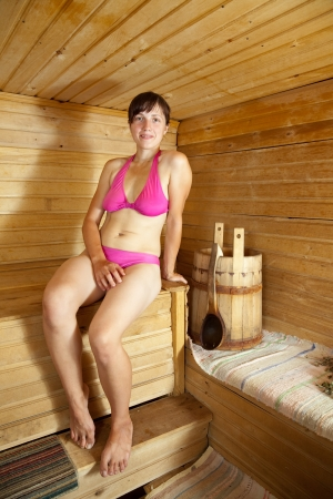 Young woman is sitting at sauna bath photo