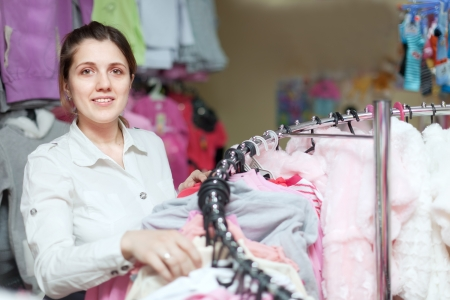 Smiling woman chooses blouse at clothing store Stock Photo - 22554151