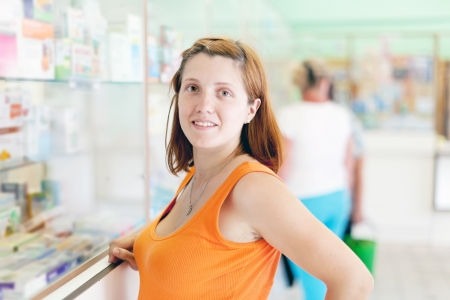 woman chooses drugs at the pharmacy drugstore photo