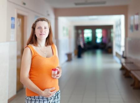 urinalysis: donna incinta con il campione delle urine presso la clinica