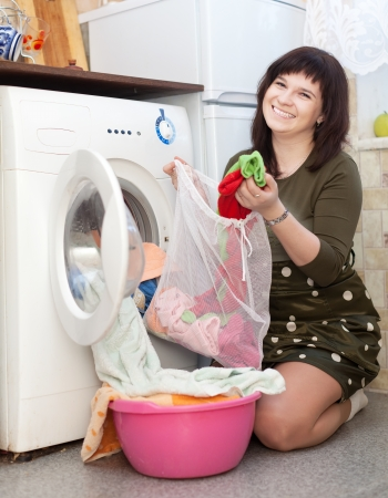 Happy woman with laundry bag  near washing machine  photo