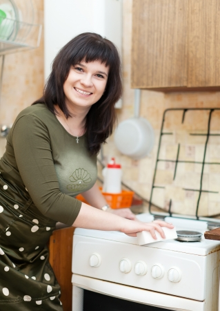 domestic task: Happy housewife cleans the gas-stove with melamine sponge  at kitchen