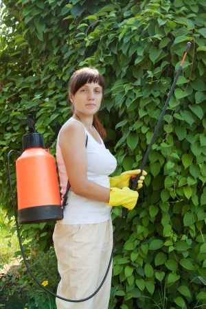 insecticidal: Female gardener working in   yard with knapsack garden spray Stock Photo