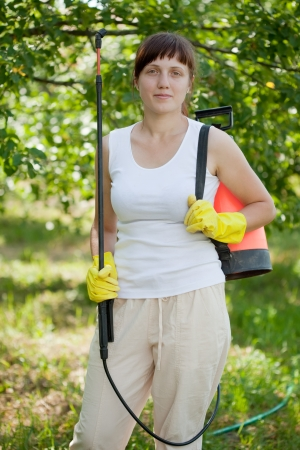 Woman holding  garden spray  in the yard photo