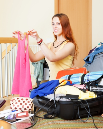 choosing clothes: Happy girl sitting  on sofa and  choosing clothes for vacation