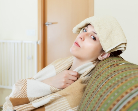 Sad young woman having headache holding towel on her head at home photo