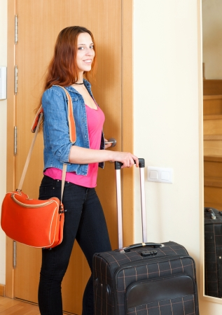 Smiling female tourist with luggage near door  photo