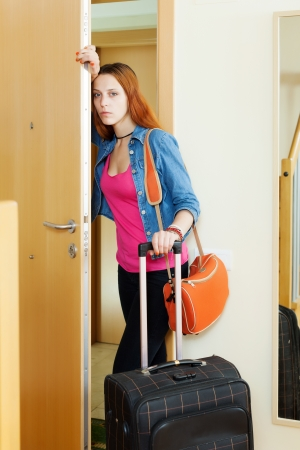 Sad woman leaving  home with suitcase because divorce photo