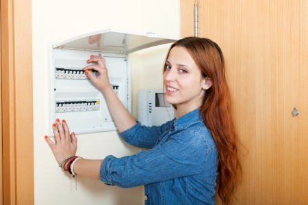 Long-haired woman turning off the light-switch at power control panel in home photo