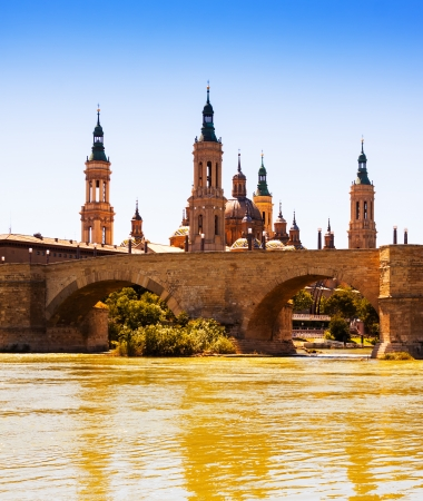 aragon:  View of Zaragoza in sunny day. Ancient stone bridge and Cathedral from river