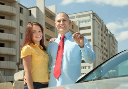 residential settlement: Outdoor portrait of   happy couple against new real estate