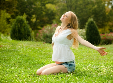gravida: Smiling pregnant woman lying on the soft grass in the summer park  Stock Photo