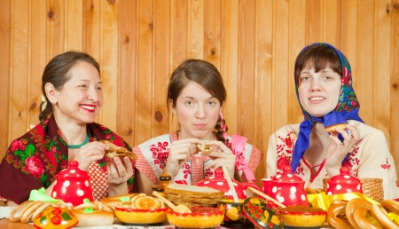 banket: Women in traditional  clothes eating pancake with caviare during  Pancake Week