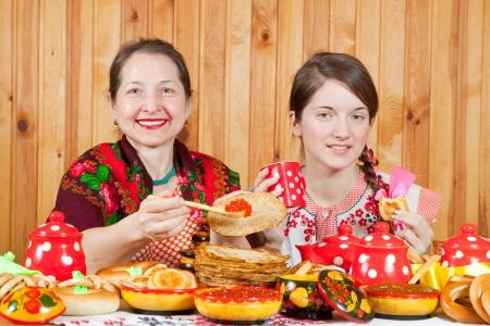 maslenitsa: Girl in traditional  clothes eating pancake during  Maslenitsa festival Stock Photo