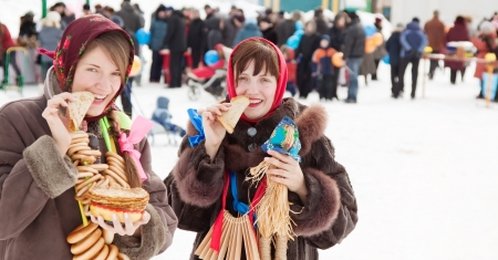 sudarium: Smiling girls in russian traditional kerchief eating pancake during  Shrovetide Stock Photo