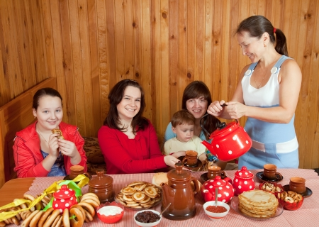 Women  with child drinks tea and eats pancake  in home photo
