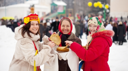 Women eating pancakes during  Maslenitsa festival in Russia Stock Photo