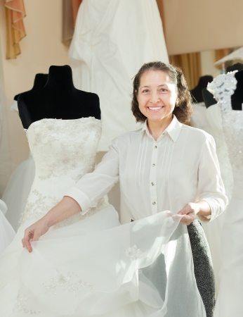 Shop assistant shows bridal dress at wedding store photo