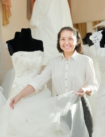 bridal salon: Shop assistant shows bridal dress at wedding store